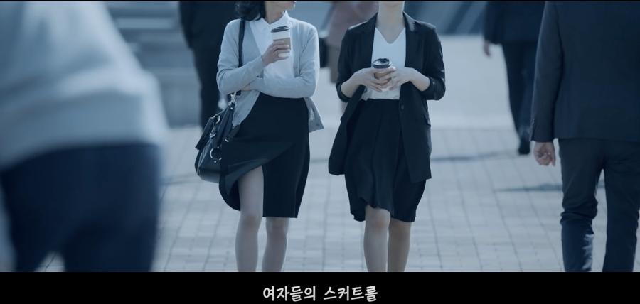 여자들이 커피를 들고 스커트를 입은 채 걸어간다.