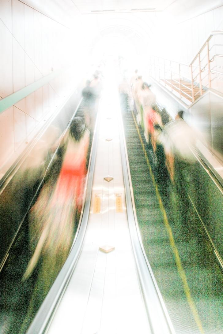 휴일오후 모습-지하철 에스컬레이터에 올라타 윗층으로 올라가는 사람들을 찍은사진. 지상에 가까워 질 수록 노출이 과다해져 하얗게 번져간다.